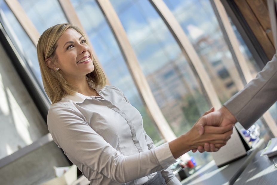 Business woman greeting a client at the office with a handshake or closing a deal