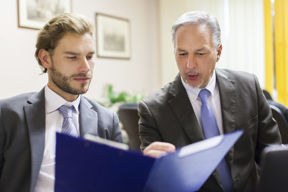 Businessman showing a document to his colleague